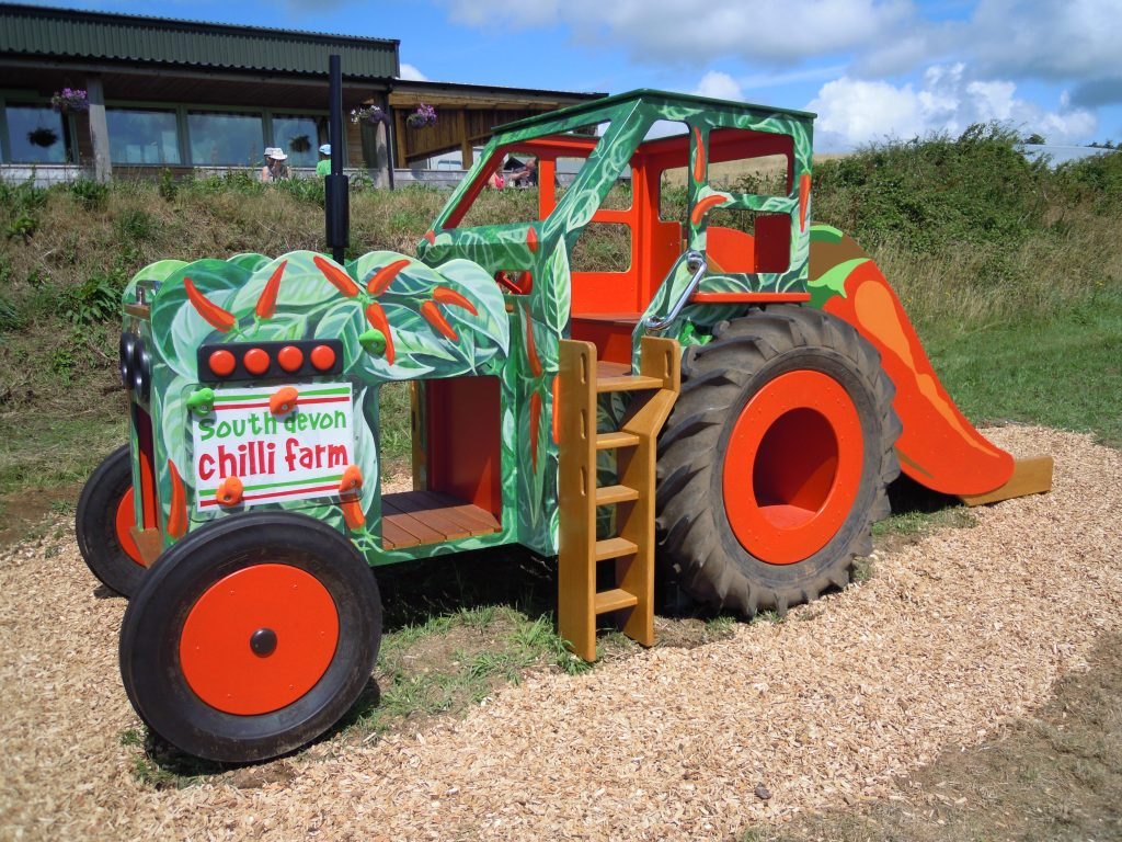 Side view (South Devon Chilli Farm childrens wooden tractor with slide and climbing apparatus)
